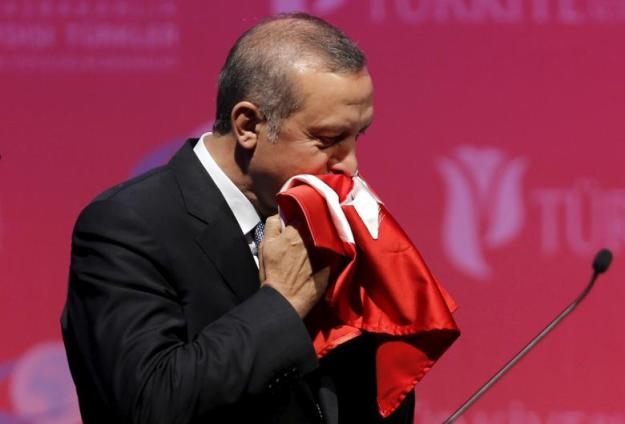 FILE PHOTO: Turkey's President Erdogan kisses a handmade Turkish flag, given him as a gift from Ugandan university student Cemil, during a graduation ceremony in Ankara, Turkey